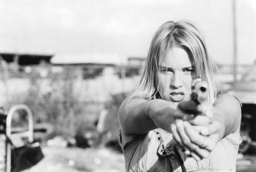 Renee Zellweger aims a gun in Love and a .45 (1994)