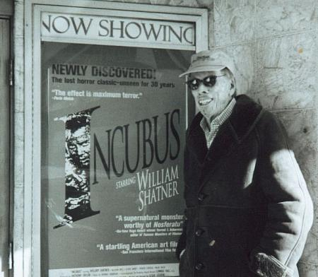 Anthony M. Taylor, producer of Incubus (1966), poses in front of a poster for the film